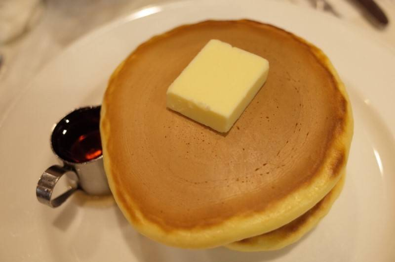 A picture of 2 layers of pancake served with butter and syrup